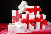 Prachtige geschenken met rode linten op donkere achtergrond — Stockfoto