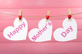 Happy Mothers Day message written on paper hearts on pink background — Stock Photo
