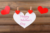 Happy Mothers Day message written on paper heart on brown background — Stock Photo