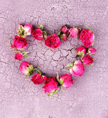 Heart of beautiful pink dried roses on old wooden background — Stock Photo