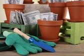 Koncepcja biznesowa: coraz pieniądze w doniczki i ogrodnictwo narzędzia na tle przyrody — Zdjęcie stockowe