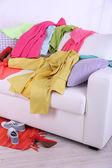 Messy colorful clothing on  sofa on light background — ストック写真