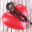 Heart with rosary beads on wooden background — Stock Photo #46304097