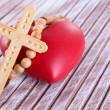 Heart with rosary beads on wooden background — Stock Photo #46304103