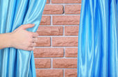 Hand opening curtain on wall background — Stock Photo