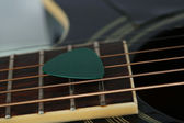 Colourful plectrum on guitar — Stock Photo