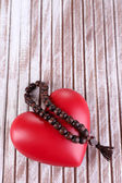 Heart with rosary beads on wooden background — Photo