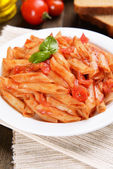 Pasta with tomato sauce on plate on table close-up — Stok fotoğraf