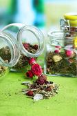 Assortimento di erbe e tè in barattoli di vetro sulla tavola di legno, su sfondo luminoso — Foto Stock