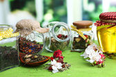 Assortment of herbs and tea and honey in glass jars on wooden table, on bright background  — Stock Photo