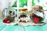 Assortment of herbs and tea in glass jars on wooden table, on bright background — Stock Photo