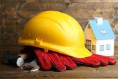 Composição com capacete de segurança, luvas de couro, ferramentas e casa decorativo no fundo de madeira — Fotografia Stock