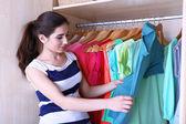 Giovane donna scegliere i vestiti nell'armadio a casa — Foto Stock