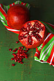 Ripe pomegranates on color wooden background — Stockfoto