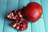 Ripe pomegranates on color wooden background — Stock Photo