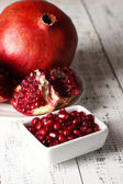 Ripe pomegranates on plate, on color wooden background — Stok fotoğraf
