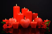 Beautiful candles with flowers isolated on black — Stock Photo