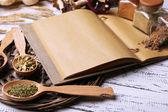 Różne przyprawy i gotować książki na drewnianym stole, z bliska — Zdjęcie stockowe