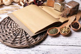 Different spices and cook book on wooden table, close up — Stok fotoğraf