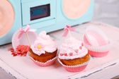 Tasty cup cakes with cream on wooden chair — Stock Photo