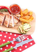 Grilled steak with fried potato pieces and grilled vegetables  on wooden board, isolated on white — Stock Photo