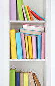Books on white shelves close-up — Stock Photo
