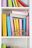 Books on white shelves close-up — Stock Photo