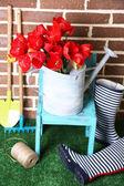 Composición de coloridos tulipanes en la regadera y botas de lluvia sobre fondo brillante — Foto de Stock