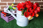 Composition of colorful tulips in watering can and equipment for gardening on bright background — Stock Photo