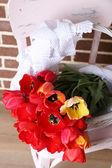 Букет красочных тюльпанов в плетеную корзину, на стуле, на фоне домашнего интерьера — Стоковое фото