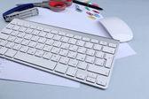 Mesa de escritório com acessórios de papelaria, o teclado e o papel, close-up — Fotografia Stock