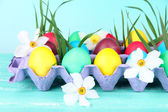 Colorful Easter eggs with grass and flowers in tray on table on bright background — Stock Photo