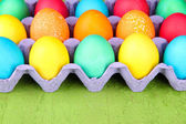 Colorful Easter eggs in tray on wooden background — Stock Photo