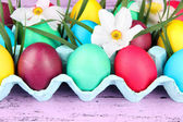 Colorful Easter eggs with grass and flowers in tray on wooden background — Stock Photo