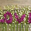 Постер, плакат: Beautiful lilac flowers and lilies of the valley on wooden background