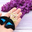 Beautiful butterfly sitting on hand and lilac flowers, on wooden background — Stock Photo #46314143