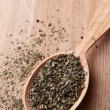 Spice greens in spoon on wooden background — Stock Photo
