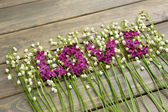 Beautiful lilac flowers and lilies of the valley, on wooden background — Photo