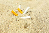 Cigarette butts  on the beach — Stock Photo