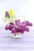 Beautiful butterflies sitting on spring flowers, on wooden table — Stock Photo