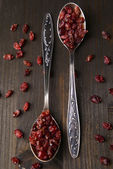 Spice barberry in spoons on wooden background — Stock Photo