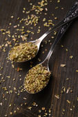 Spice greens in spoons on wooden background — Stock Photo