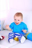 милый маленький мальчик, играя на диване в комнате — Стоковое фото