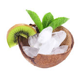 Fruit slices and ice cubes in coconut shell isolated on white. Cold drinks concept — Stock Photo