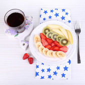 Various sliced fruits on plate on table close-up — Stock Photo