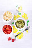 Various sliced fruits in bowls on table close-up — Stock Photo