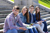 Happy students sitting on stairs in park — Stock Photo