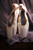 Ballet pointe shoes on fabric background — Stock Photo