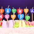 Birthday cake with candles on violet background — Stock Photo #46439807