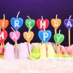 bolo de aniversário com velas em fundo violeta — Fotografia Stock  #46439807
